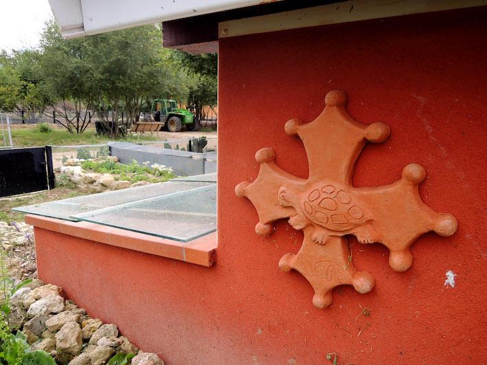 Visuel du Refuge des Tortues composé à partir d'une croix occitane ou croix du Languedoc ou encore, croix de Toulouse et d'une tortue stylisée. Le néophyte comprend très vite que le Refuge se situe dans le sud de la France (sud-ouest), dans la région de Toulouse au soleil clément. Photo : Jérôme Maran